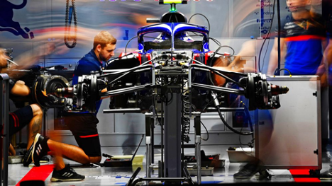 Formula One engineers working on engines in shop
