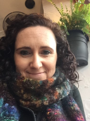 Photo of Misty Johannsen, person with curly hair and colourful scarf smiling