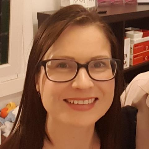 Photo of Nina Thomas, person with brown straight hair and glasses smiling